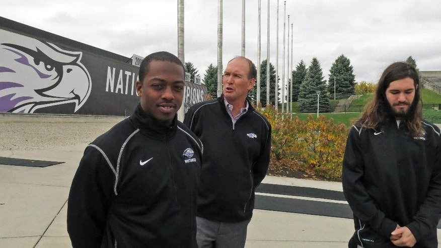 In this Oct. 21, 2014, photo, Wisconsin-Whitewater coach Lance Leipold, rear, speaks with  running back Ryan Givens, left, and receiver Jake Kumerow  in Whitewater, Wis. The Division III coach reached 100 career wins in 106 games, the fastest to the 100-win plateau in NCAA history. (AP Photo/Genaro C. Armas)