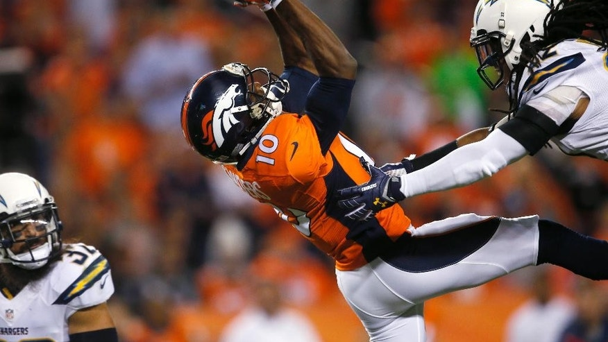 Denver Broncos wide receiver Emmanuel Sanders (10) makes a catch as San Diego Chargers' Eric Weddle, left, and Jason Verrett defend during the first half of an NFL football game, Thursday, Oct. 23, 2014, in Denver. (AP Photo/Joe Mahoney)