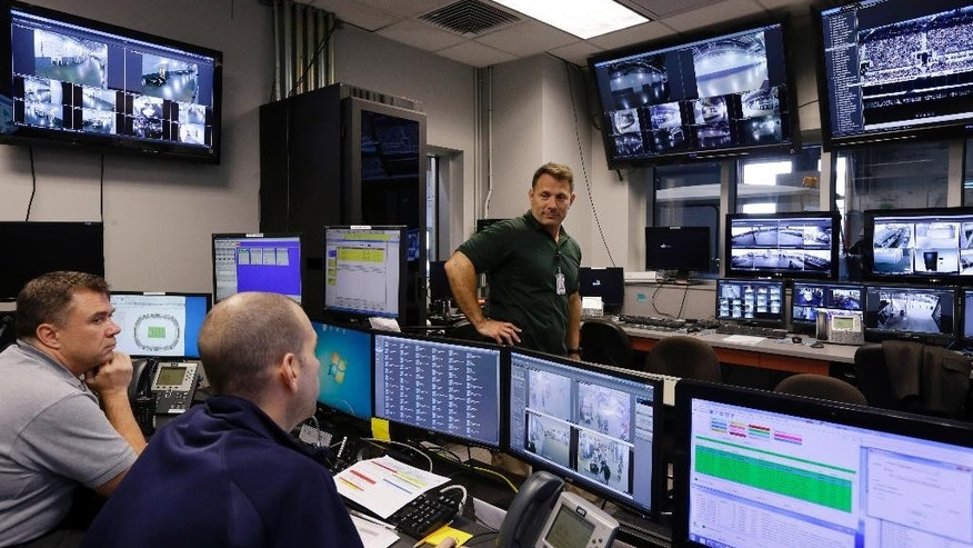 In this Oct. 15, 2014, photo, Daniel DeLorenzi, right, director of security and safety services at MetLife Stadium, talks with others in the stadium's command center in East Rutherford, N.J. Suppose a shoving match breaks out in a section of the MetLife Stadium stands. While security officers hustle to the scene, a beyond state-of-the-art surveillance system is recording every detail. (AP Photo/Mel Evans)