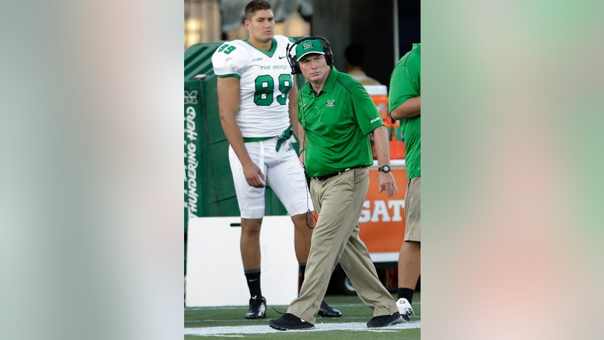 Marshall coach Doc Holliday walks on the sideline during the first half of an NCAA college football game against Florida International, Saturday, Oct. 18, 2014, in Miami. (AP Photo/Alan Diaz)
