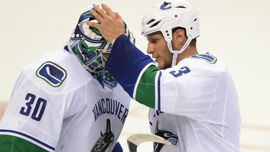 Vancouver Canucks' goalie Ryan Miller (30) is congratulated by Kevin Bieksa (3) after the Canucks' victory 4-1 victory over the St. Louis Blues in an NHL hockey game, Thursday, Oct. 23, 2014, in St. Louis. (AP Photo/Bill Boyce)