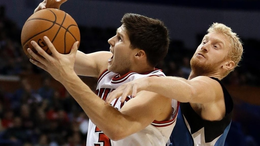 Chicago Bulls' Doug McDermott, left, is fouled on his way to the basket by Minnesota Timberwolves' Chase Budinger during the first half of a preseason NBA basketball game Friday, Oct. 24, 2014, in St. Louis. (AP Photo/Jeff Roberson)