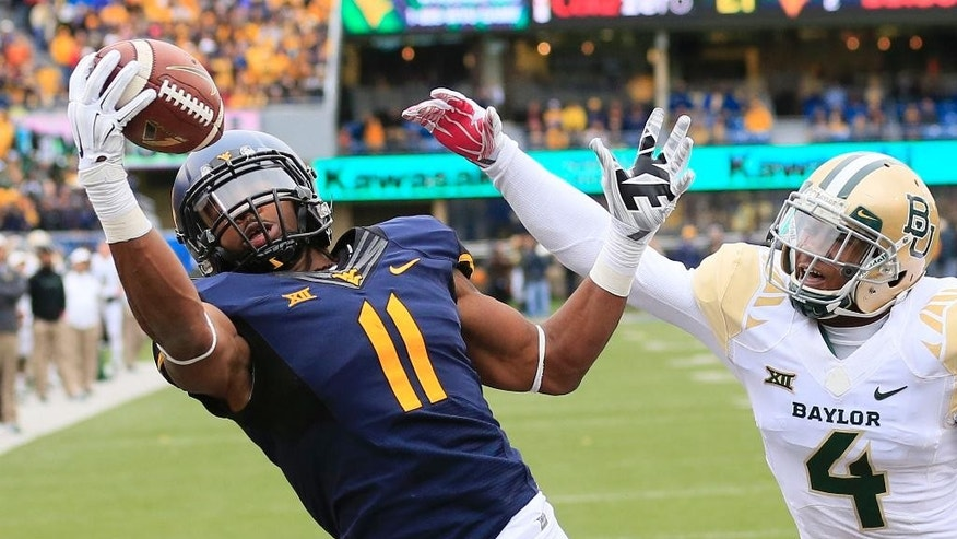 West Virginia's Kevin White (11) catches a pass for a touchdown over Baylor's Xavien Howard (4) in the fourth quarter of an NCAA college football game in Morgantown, W.Va., Saturday, Oct. 18, 2014. (AP Photo/Chris Jackson)