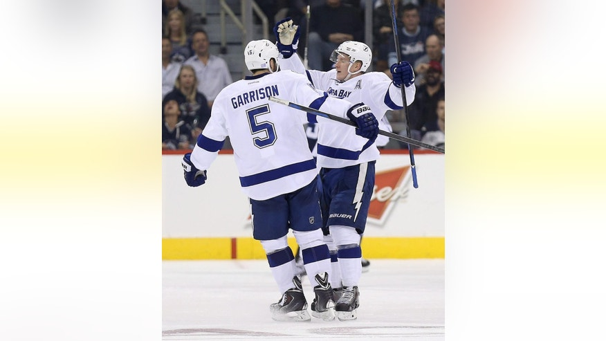 Tampa Bay Lightning's Jason Garrison (5) and Ondrej Palat celebrate after Palat scored against the Winnipeg Jets during the second period of an NHL hockey game Friday, Oct. 24, 2014, in Winnipeg, Manitoba. (AP Photo/The Canadian Press, Trevor Hagan)
