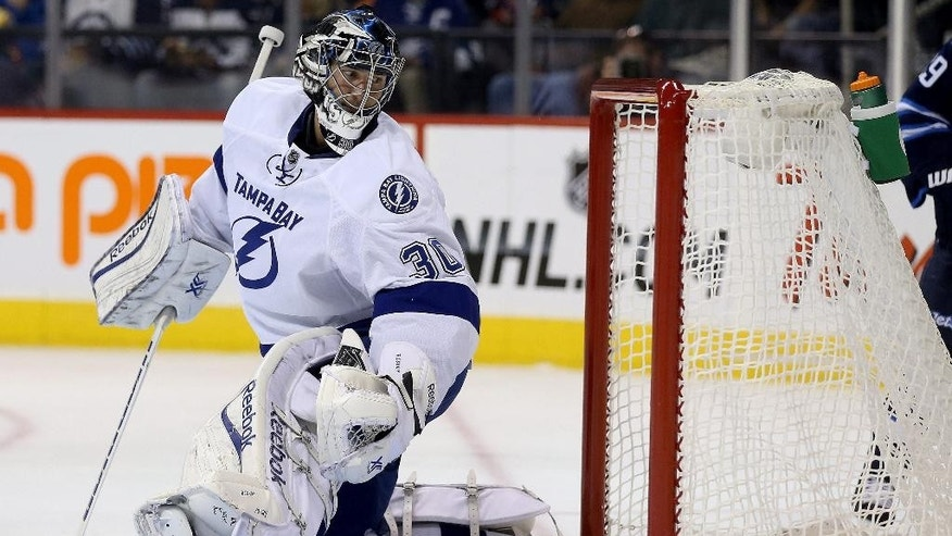 Tampa Bay Lightning goaltender Ben Bishop looks at the puck in the net after Winnipeg Jets' Bryan Little scored during the second period of an NHL hockey game Friday, Oct. 24, 2014, in Winnipeg, Manitoba. (AP Photo/The Canadian Press, Trevor Hagan)