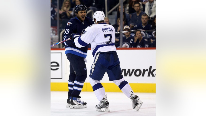 Winnipeg Jets' Dustin Byfuglien (33) battles with Tampa Bay Lightning Radko Gudas (7) during the second period of an NHL hockey game Friday, Oct. 24, 2014, in Winnipeg, Manitoba. (AP Photo/The Canadian Press, Trevor Hagan)