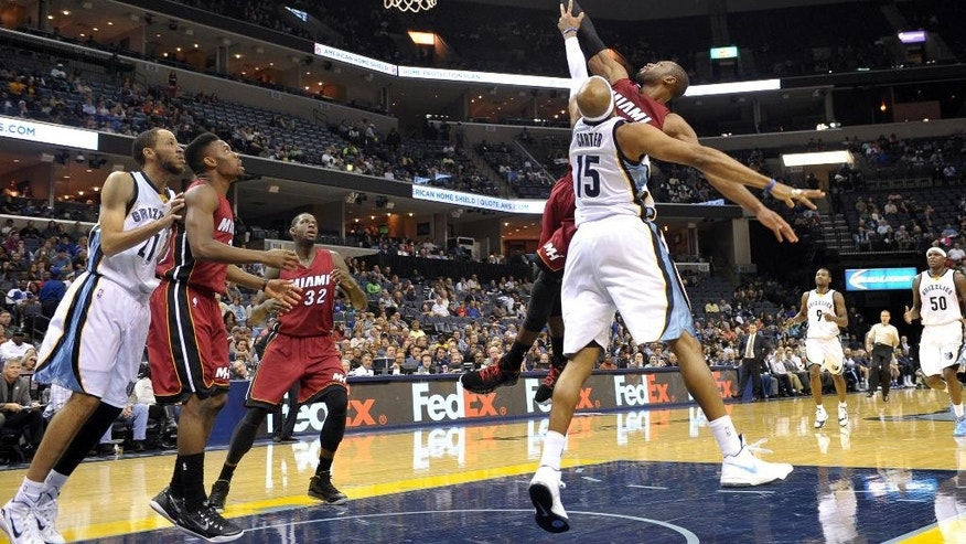 Miami Heat guard Dwyane Wade shoots over Memphis Grizzlies guard Vince Carter (15) in the first half of a preseason NBA basketball game Friday, Oct. 24, 2014, in Memphis, Tenn. (AP Photo/Brandon Dill)