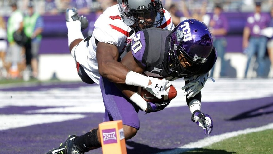 TCU wide receiver Deante' Gray (20) comes down with a touchdown reception in the end zone as Texas Tech defensive back Austin Stewart (8) defends  in the first half of an NCAA college football game, Saturday, Oct. 25, 2014, in Fort Worth, Texas. (AP Photo/Tony Gutierrez)