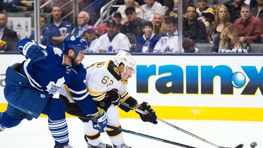 Toronto Maple Leafs defenseman Roman Polak, left, battles for the puck against Boston Bruins forward Brad Marchand (63) during first period NHL hockey action in Toronto on Saturday, Oct. 25, 2014. (AP Photo/The Canadian Press, Nathan Denette)
