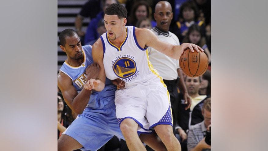 Golden State Warriors' Klay Thompson (11) drives against Denver Nuggets' Arron Affalo during the first half of a preseason NBA basketball game, Friday, Oct. 24, 2014 in Oakland, Calif. (AP Photo/George Nikitin)