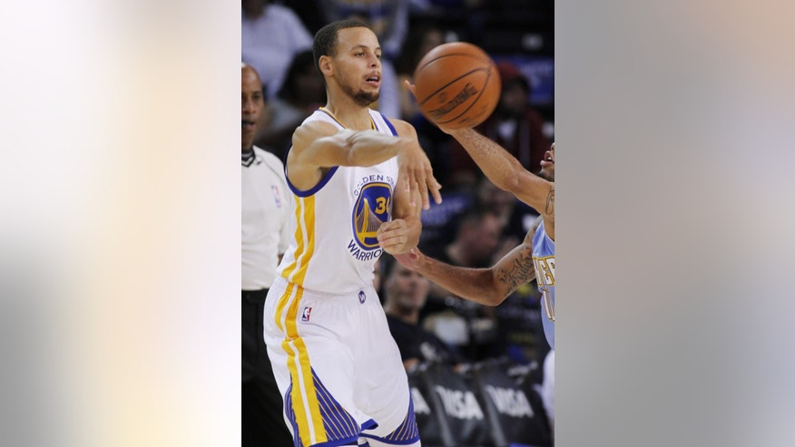 Golden State Warriors' Stephen Curry passes the ball during the first half of a preseason NBA basketball game against the Denver Nuggets, Friday, Oct. 24, 2014 in Oakland, Calif. (AP Photo/George Nikitin)
