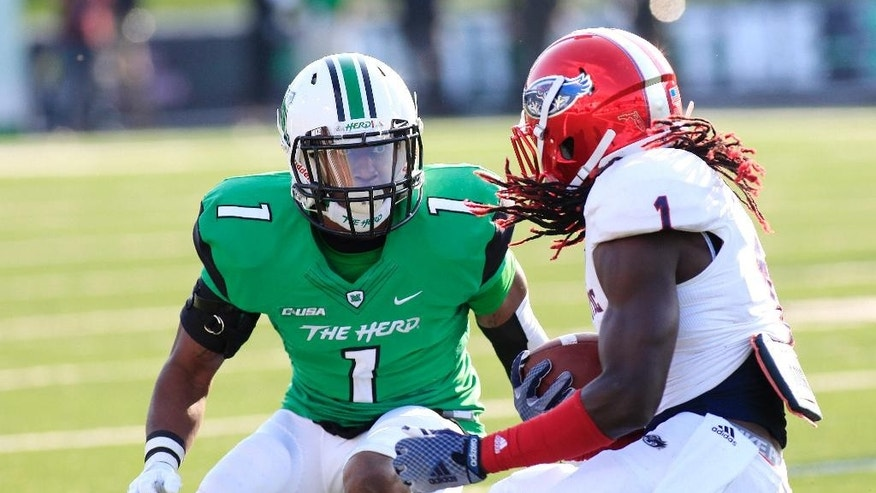 Marshall's A.J. Leggett stops Florida Atlantic's Lucky Whitehead following a pass reception, Saturday, Oct. 25, 2014 during an NCAA college football game in Huntington, W.Va. (AP Photo/Randy Snyder)