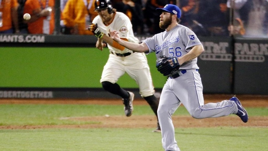 Kansas City Royals' Greg Holland throws to first for the final out on San Francisco Giants' Hunter Pence during the ninth inning of Game 3 of baseball's World Series Friday, Oct. 24, 2014, in San Francisco. The Royals won the game 3-2 to lead the series 2-1. (AP Photo/Charlie Riedel)