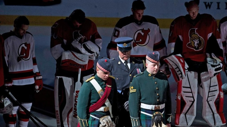 Ottawa Senators and New Jersey Devils players stand shoulder to shoulder around members of the Argyle and Sutherland Highlanders during a minute of silence before an NHL hockey game, Saturday, Oct. 25, 2014 in Ottawa, Ontario. (AP Photo/The Canadian Press, Adrian Wyld)