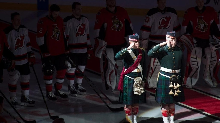 Ottawa Senators and New Jersey Devils players stand shoulder to shoulder around members of the Argyle and Sutherland Highlanders during the playing of 'O Canada' before an NHL hockey game, Saturday, Oct. 25, 2014 in Ottawa, Ontario. (AP Photo/The Canadian Press, Adrian Wyld)