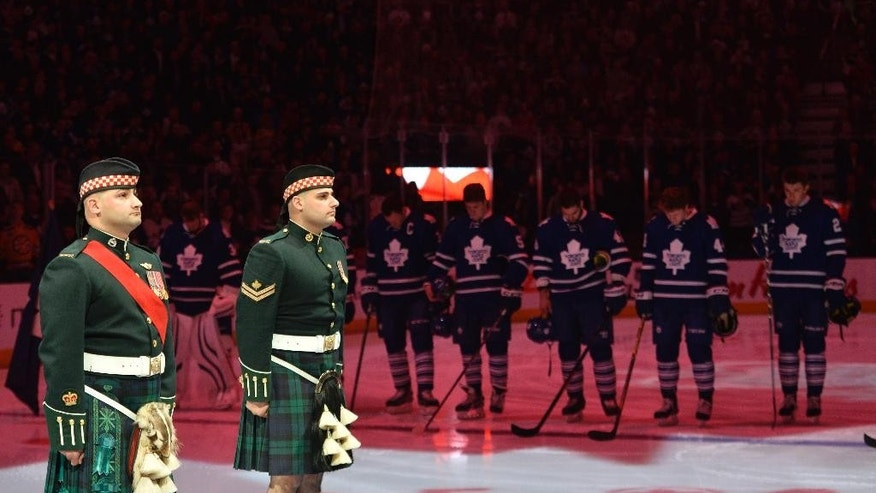 Members of the Canadian Forces, along with players and fans, observe a moment of silence as they take part in a ceremony honoring two fallen soldiers in the recent attacks on Canadian soil before NHL hockey game action between the Toronto Maple Leafs and the Boston Bruins in Toronto, Saturday, Oct. 25, 2014. (AP Photo/The Canadian Press, Nathan Denette)