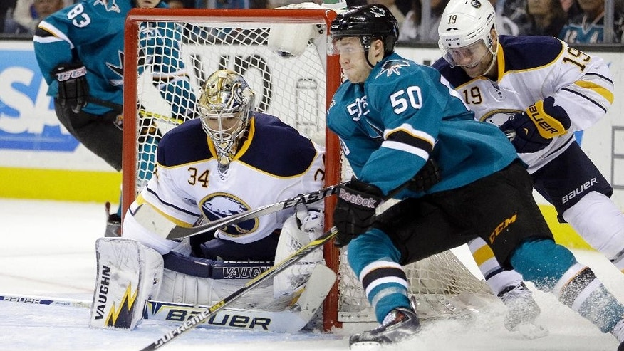 San Jose Sharks' Chris Tierney (50) waits for a pass to take a shot against Buffalo Sabres goalie Michal Neuvirth (34) during the second period of an NHL hockey game Saturday, Oct. 25, 2014, in San Jose, Calif. At right is Sabres' Cody Hodgson (19). (AP Photo/Ben Margot)