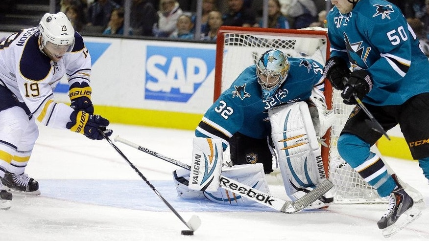 Buffalo Sabres' Cody Hodgson, left, maneuvers the puck before scoring against San Jose Sharks goalie Alex Stalock (32) during the third period of an NHL hockey game Saturday, Oct. 25, 2014, in San Jose, Calif. At right is Sharks' Chris Tierney. The Sabres won 2-1.(AP Photo/Ben Margot)