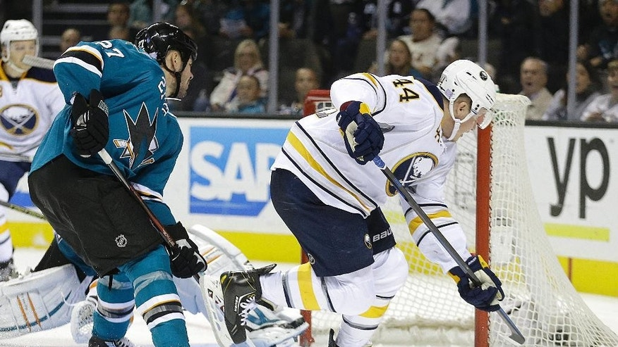 Buffalo Sabres' Nicolas Deslauriers (44) scores a goal past San Jose Sharks' Scott Hannan (27) during the third period of an NHL hockey game Saturday, Oct. 25, 2014, in San Jose, Calif. The Sabres won 2-1. (AP Photo/Ben Margot)