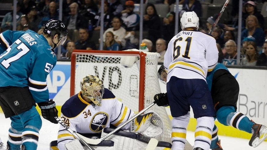 Buffalo Sabres goalie Michal Neuvirth (34) and Andre Benoit (61) block a shot from San Jose Sharks' Adam Burish, right, during the second period of an NHL hockey game Saturday, Oct. 25, 2014, in San Jose, Calif. At left is Sharks' Tommy Wingels (57). (AP Photo/Ben Margot)