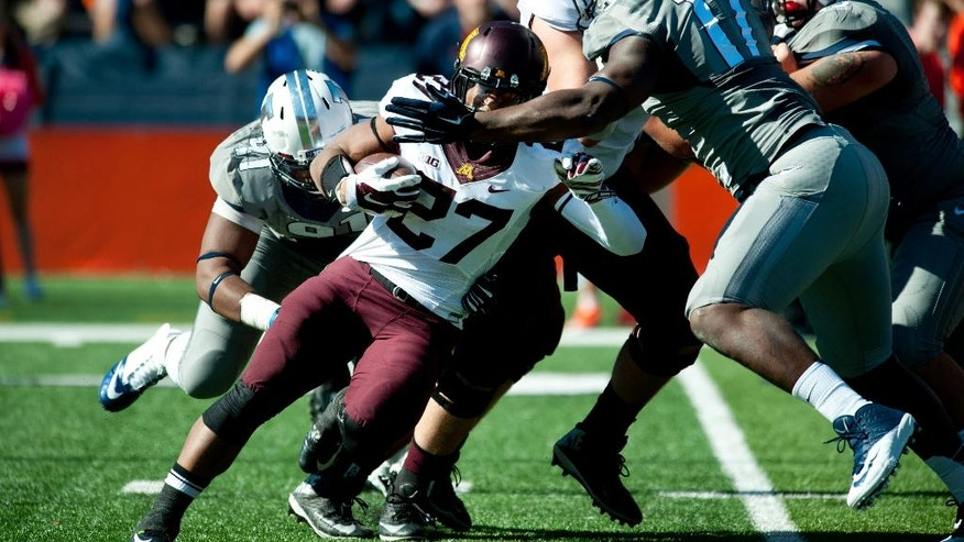 Minnesota running back David Cobb (27) is tackled by Illinois defensive lineman Jihad Ward (17) during the first half of an NCAA football game Saturday, Oct. 25, 2014, at Memorial Stadium in Champaign, Ill. (AP Photo/Bradley Leeb)