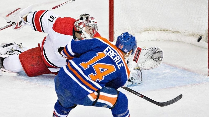 Edmonton Oilers' Jordan Eberle (14) scores on Carolina Hurricanes' Anton Khudobin (31) during the second period of an NHL hockey game Friday, Oct. 24, 2014, in Edmonton, Alberta. (AP Photo/The Canadian Press, Jason Franson)
