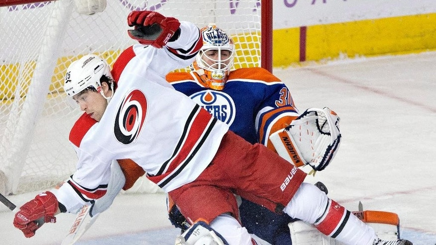 Carolina Hurricanes' Chris Terry (25) crashes into Edmonton Oilers goalie Ben Scrivens (30) during the second period of an NHL hockey game Friday, Oct. 24, 2014, in Edmonton, Alberta. (AP Photo/The Canadian Press, Jason Franson)