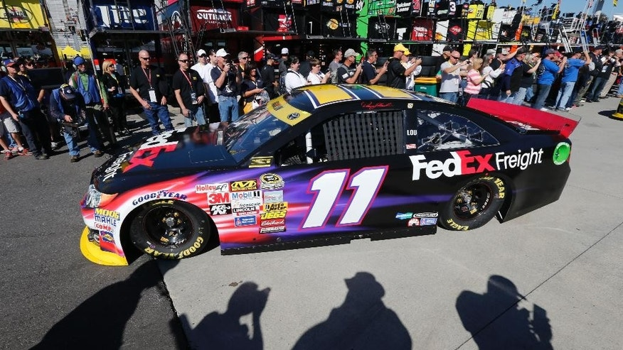 Denny Hamlin (11) makes his way out of the garage at Martinsville Speedway in Martinsville, Va., Saturday, Oct. 25, 2014, to practice for Sunday's Sprint Cup Series auto race. (AP Photo/Steve Helber)