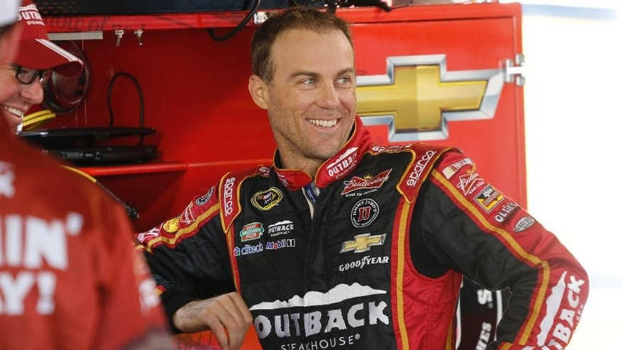 Kevin Harvick talks to his crew in the garage as he waits for practice to begin for Sunday's Sprint Cup Series auto race at Martinsville Speedway in Martinsville, Va., Saturday, Oct. 25, 2014. (AP Photo/Steve Helber)