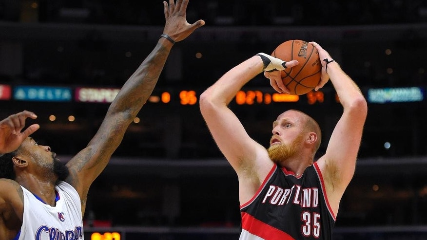 Portland Trail Blazers center Chris Kaman shoots as Los Angeles Clippers center DeAndre Jordan defends during the second half of a preseason NBA basketball game, Friday, Oct. 24, 2014, in Los Angeles. The Trail Blazers won 99-89. (AP Photo/Mark J. Terrill)
