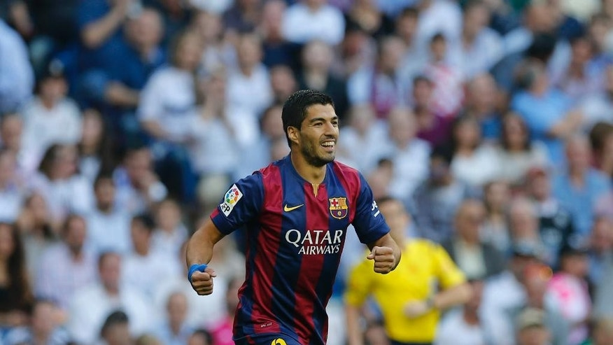 CORRECTING PLAYER WHO SCORED TO NEYMAR - Barcelona's Luis Suarez, celebrates after Barcelona teammate Neymar scored during a Spanish La Liga soccer match between Real Madrid and Barcelona at the Santiago Bernabeu stadium in Madrid, Spain, Saturday Oct. 25, 2014. (AP Photo/Paul White)
