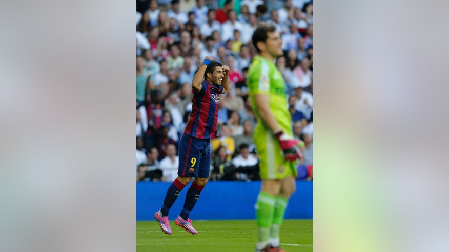 Barcelona's Luis Suarez, left, celebrates after Barcelona's Lionel Messi scored during a Spanish La Liga soccer match between Real Madrid and Barcelona at the Santiago Bernabeu stadium in Madrid, Spain, Saturday Oct. 25, 2014. (AP Photo/Paul White)