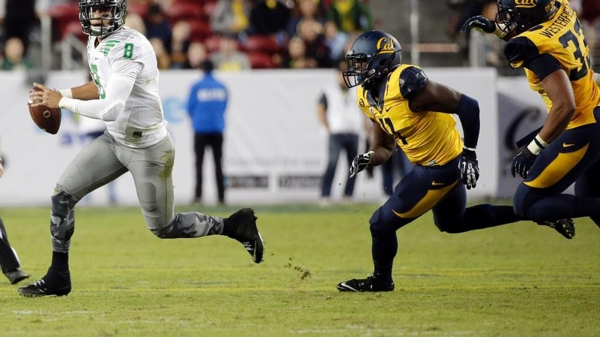Oregon quarterback Marcus Mariota, left, is chased by California's Jonathan Johnson, center, and Noah Westerfield during the first half of an NCAA college football game Friday, Oct. 24, 2014, in Santa Clara, Calif. (AP Photo/Marcio Jose Sanchez)