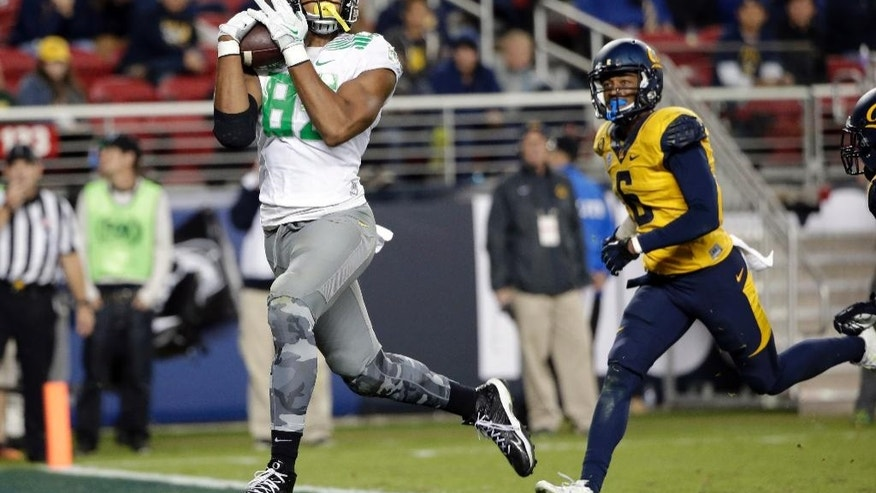 Oregon tight end Pharaoh Brown, left, catches a touchdown pass next to California cornerback Darius White during the second half of an NCAA college football game Friday, Oct. 24, 2014, in Santa Clara, Calif. (AP Photo/Marcio Jose Sanchez)