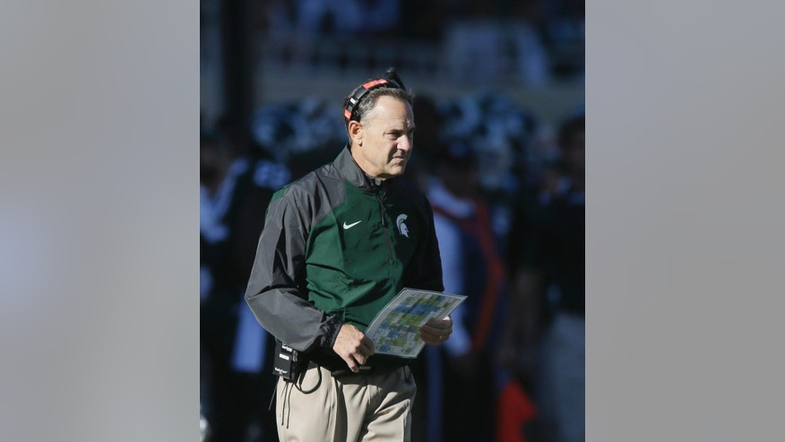 Michigan State head coach Mark Dantonio walks the sidelines during the first half of an NCAA college football game against Michigan in East Lansing, Mich., Saturday, Oct. 25, 2014. (AP Photo/Carlos Osorio)