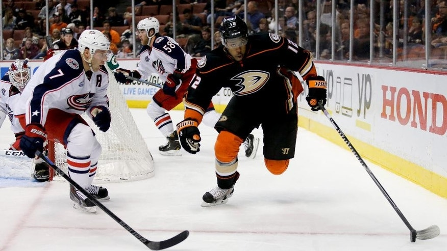Columbus Blue Jackets defenseman Jack Johnson, left, watches Anaheim Ducks right wing Devante Smith-Pelly reach for the puck during the second period of an NHL hockey game in Anaheim, Calif., Friday, Oct. 24, 2014. (AP Photo/Chris Carlson)