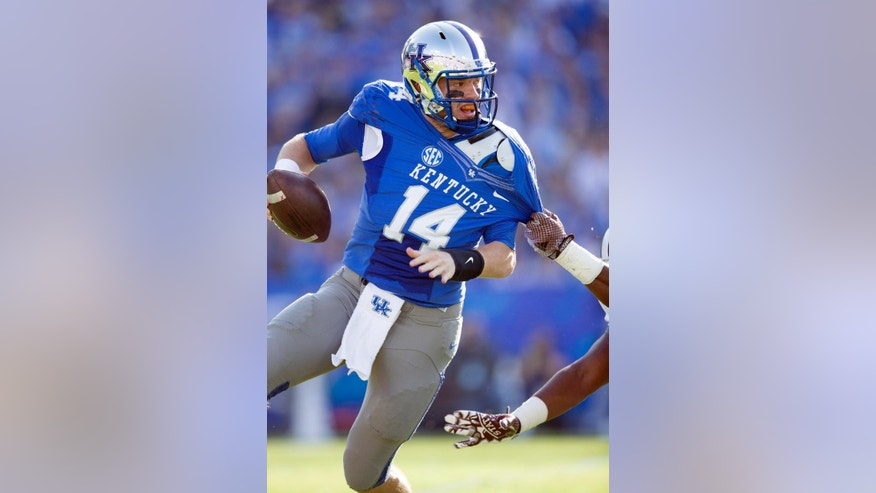 Kentucky quarterback Patrick Towles scrambles to get away from the Mississippi State defense during the first half of an NCAA college football game at Commonwealth Stadium in Lexington, Ky., Saturday, Oct. 25, 2014. (AP Photo/David Stephenson)