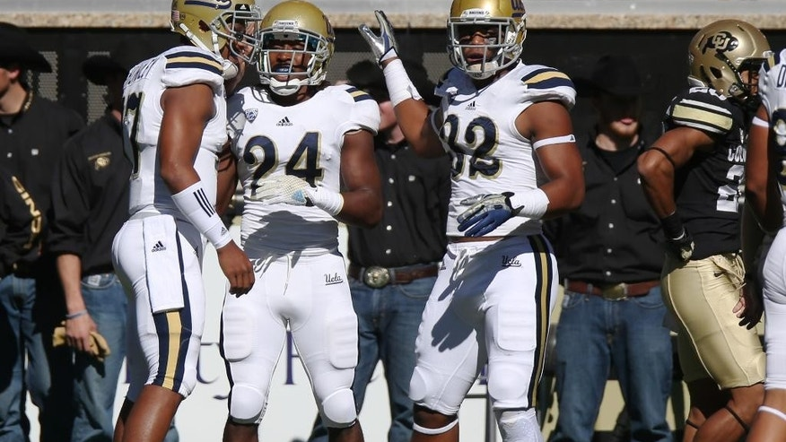 From left, UCLA quarterback Brett Hundley celebrates with running back Paul Perkins and fullback Nate Iese after Perkins' 93-yard touchdown run as Colorado defensive back Greg Henderson walks away in the first quarter of an NCAA football game in Boulder, Colo., on Saturday, Oct. 25, 2014. (AP Photo/David Zalubowski)