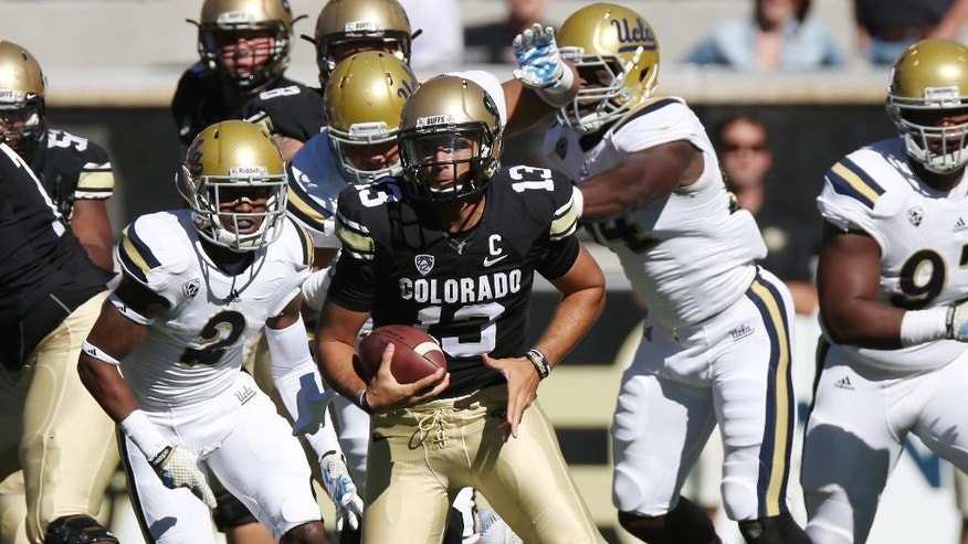 Colorado quarterback Sefo Liufau, right, runs for yardage as UCLA  defensive back Jaleel Wadood (2) chases in the first quarter of an NCAA college football game in Boulder, Colo., Saturday, Oct. 25, 2014. (AP Photo/David Zalubowski)