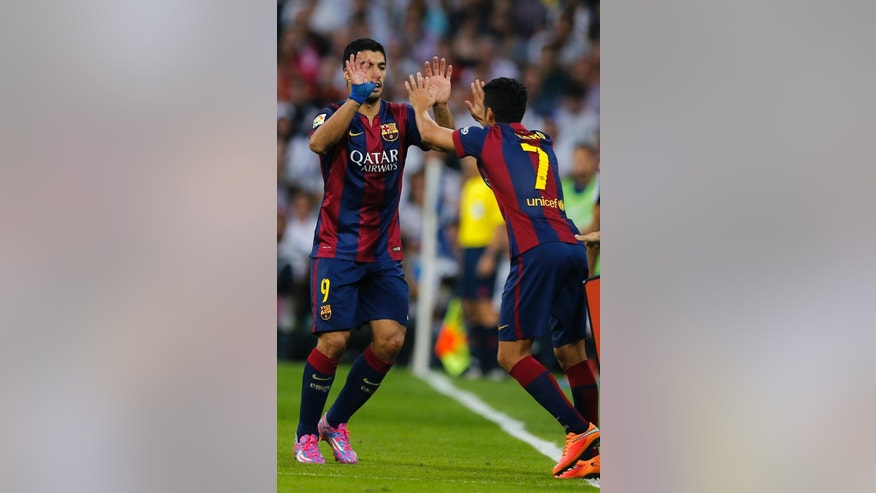 Barcelona's Luis Suarez, left, leaves the pitch, to be replaced by Barcelona's Pedro Rodriguez after being substituted during a Spanish La Liga soccer match between Real Madrid and Barcelona at the Santiago Bernabeu stadium in Madrid, Spain, Saturday Oct. 25, 2014. (AP Photo/Paul White)