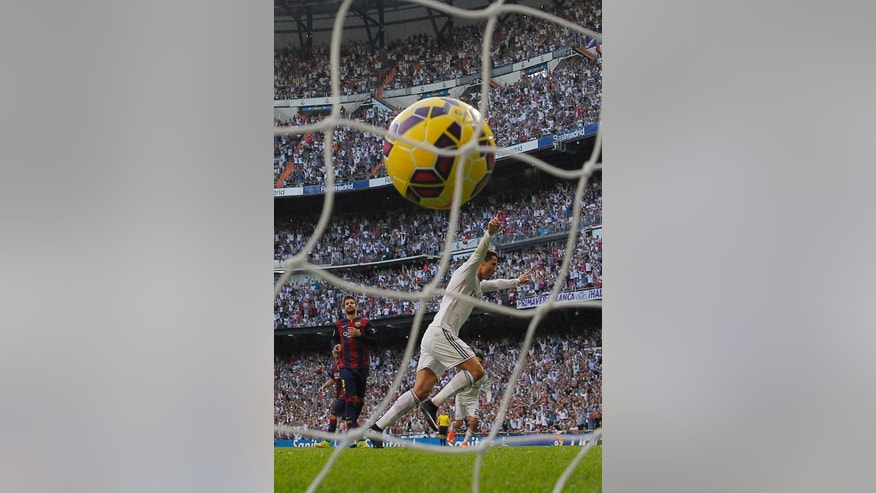 Real Madrid's Cristiano Ronaldo, right, celebrates his goal during a Spanish La Liga soccer match between Real Madrid and FC Barcelona at the Santiago Bernabeu stadium in Madrid, Spain, Saturday, Oct. 25, 2014. (AP Photo/Andres Kudacki)