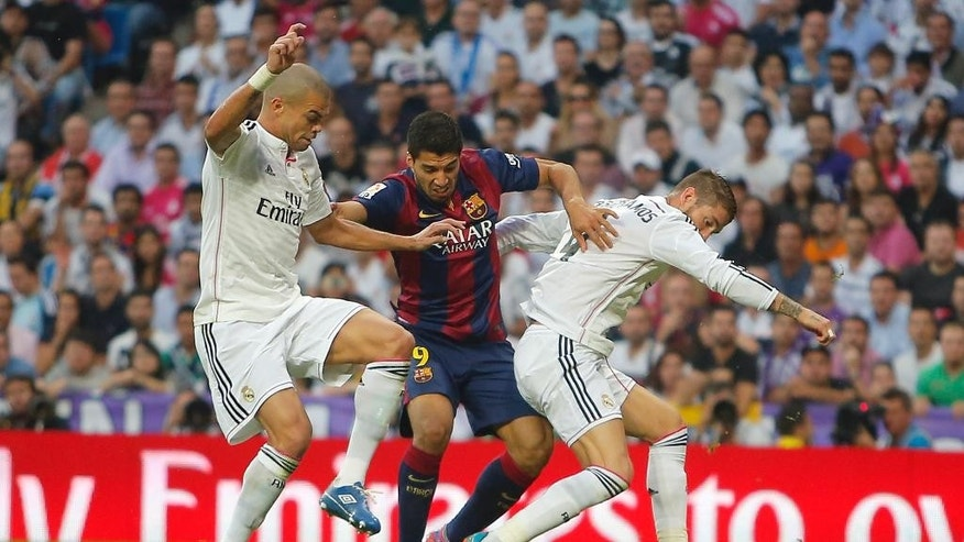 Barcelona's Luis Suarez, centre, in action with Real Madrid's Karim Benzema, left, and Real Madrid's Sergio Ramos, right,  during a Spanish La Liga soccer match between Real Madrid and FC Barcelona at the Santiago Bernabeu stadium in Madrid, Spain, Saturday, Oct. 25, 2014. (AP Photo/Andres Kudacki)