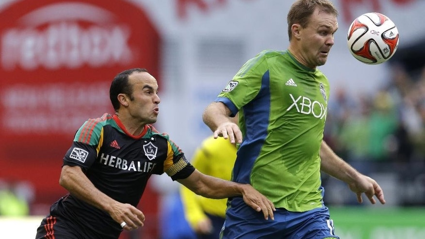 Los Angeles Galaxy midfielder Landon Donovan, left, battles for the ball with Seattle Sounders defender Chad Marshall, right, during the first half of an MLS soccer match, Saturday, Oct. 25, 2014, in Seattle. (AP Photo/Ted S. Warren)