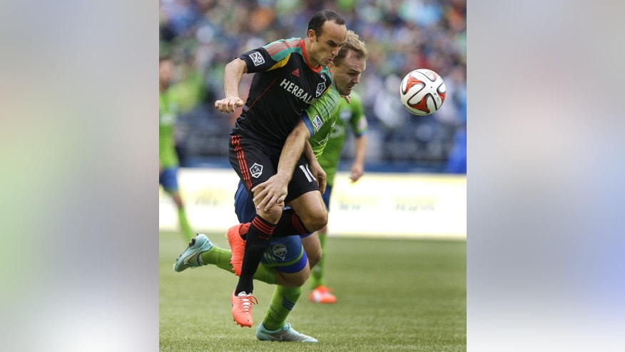 Los Angeles Galaxy midfielder Landon Donovan, left, tangles with Seattle Sounders defender Chad Marshall, right, as they chase a loose ball during the first half of an MLS soccer match, Saturday, Oct. 25, 2014, in Seattle. (AP Photo/Ted S. Warren)