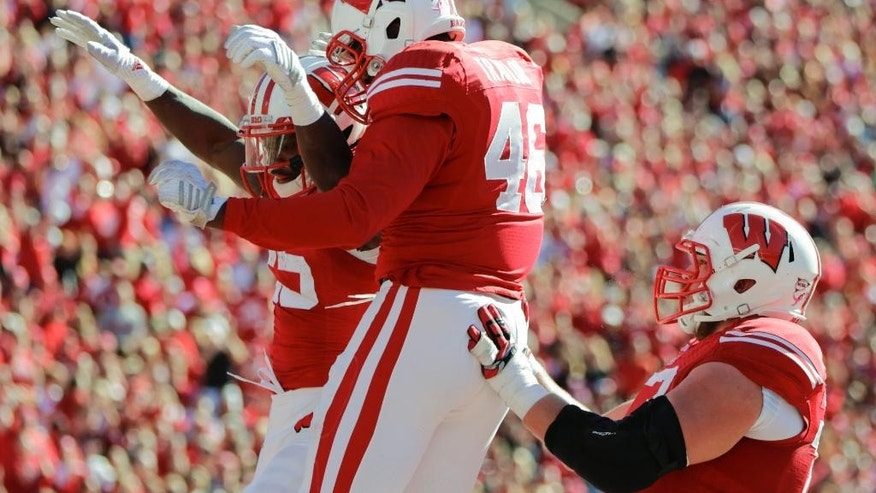 Wisconsin running back Melvin Gordon, left, celebrates with teammates Austin Traylor (46) and Kyle Costigan during the first half of an NCAA college football game Saturday, Oct. 25, 2014, in Madison, Wis. (AP Photo/Andy Manis)