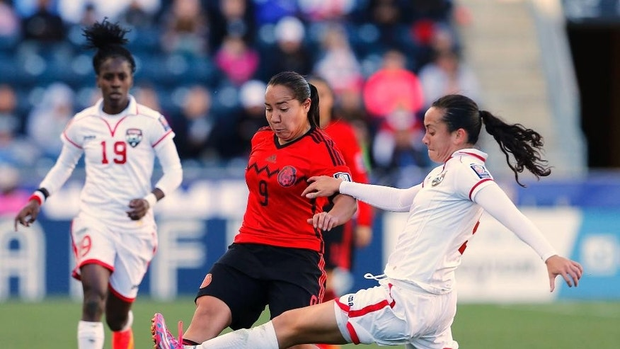 Mexico forward Veronica Charlyn Corral (9) attempts to move the ball past Trinidad and Tobago defender Arin King (5) in overtime during a CONCACAF consolation soccer match in Chester, Pa., Sunday, Oct. 26, 2014. Mexico defeated Trinidad and Tobago 4-2 in overtime. (AP Photo/Rich Schultz)
