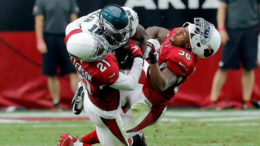 Philadelphia Eagles wide receiver Jeremy Maclin, center, is hit by Arizona Cardinals cornerback Patrick Peterson (21) and Deone Bucannon (36) during the first half of an NFL football game, Sunday, Oct. 26, 2014, in Glendale, Ariz. Peterson was injured on the play. (AP Photo/Rick Scuteri)