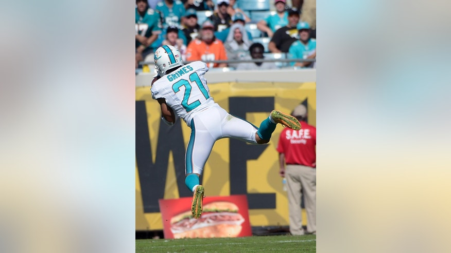 Miami Dolphins cornerback Brent Grimes intercepts a pass and returns it 22 yards for a touchdown during the first half of an NFL football game against the Jacksonville Jaguars in Jacksonville, Fla., Sunday, Oct. 26, 2014. (AP Photo/Phelan M. Ebenhack)
