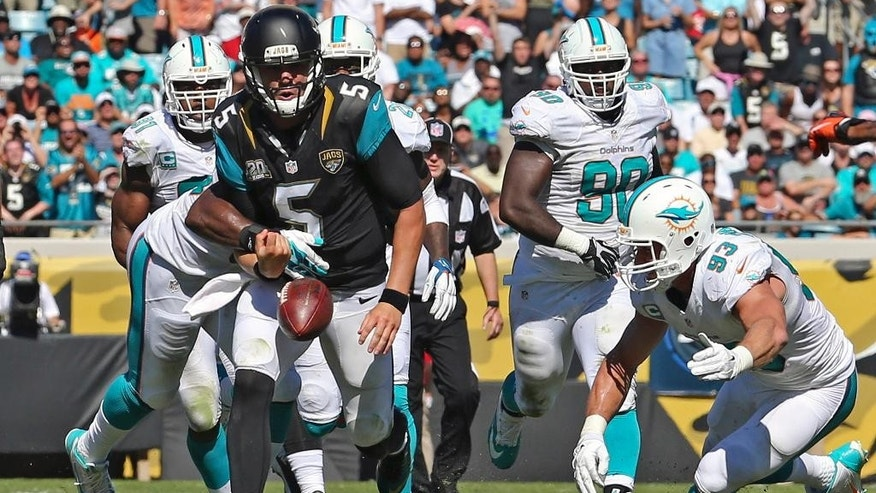 Jacksonville Jaguars quarterback Blake Bortles (5) fumbles the ball as he tries to run through the Miami Dolphins defense including defensive tackle Earl Mitchell (90) and middle linebacker Jason Trusnik (93) during the first half of an NFL football game in Jacksonville, Fla., Sunday, Oct. 26, 2014. (AP Photo/Gary McCullough)