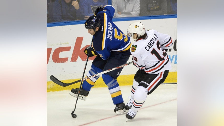 St. Louis Blues' Barret Jackman (5) and Chicago Blackhawks' Daniel Carcillo (13) vie for the puck during the second period of an NHL hockey game, Saturday, Oct. 25, 2014, in St. Louis. (AP Photo/Bill Boyce)